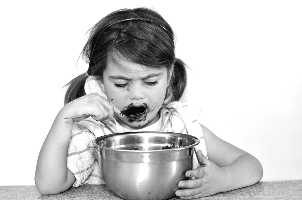 Bild: Kind beim Naschen ganz in sich versunken